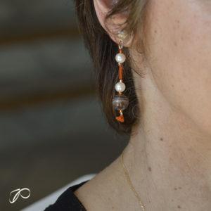Photo portée d'une création de boucles d'oreilles en perles de culture, agate du Botswana et soie orangée